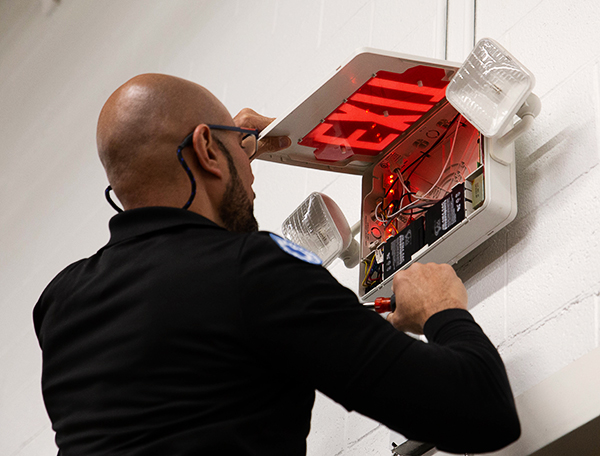 Tech Repairing an Exit and Emergency Light